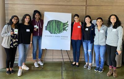 Seven students stand smiling around a poster with the Women in Data Science Berkeley logo.